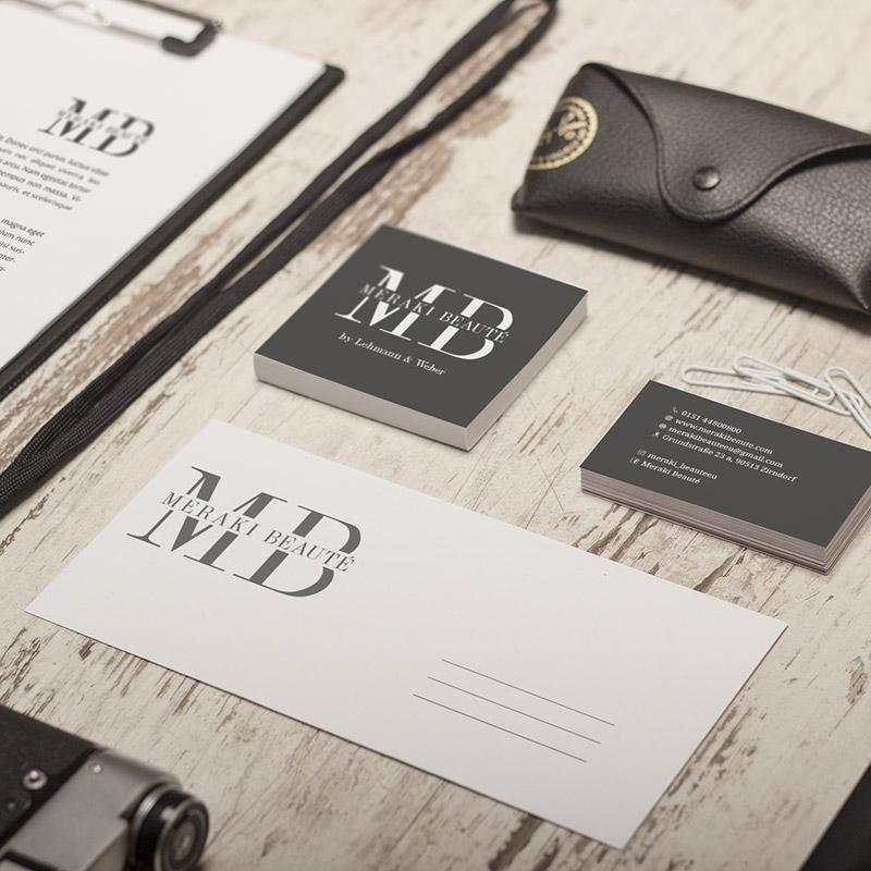 Auf dem Bild sind verschiedene Unternehmensunterlagen zu sehen, auf denen das Logo abgebildet ist. Symetrisch angeordnet auf einem Holzuntergrund.