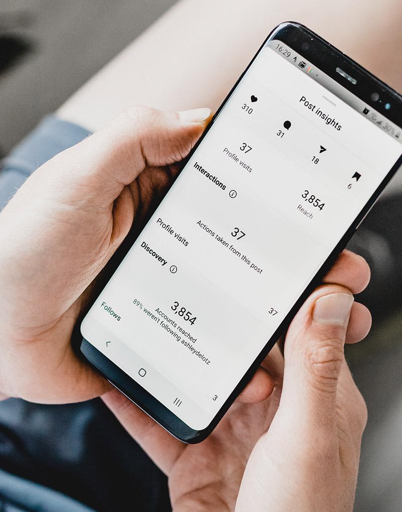 Auf dem Bild wird ein Smartphone in der Hand gehalten, welches eine Social Media-Plattform anzeigt. Es deutet auf die digitale Sichtbarkeit über soziale Medien hin, welche über effektive Multikanal- und Marketingstrategien gesteuert werden können.