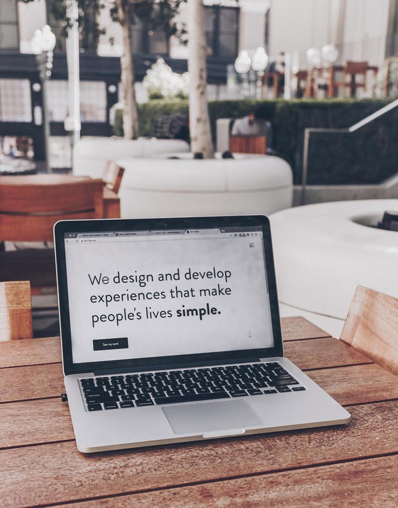 """Ein Laptop auf dem der Text """"We design and develop experiences that make people's lives simple."""" Als Sinnbild für die Erstellung und Betreuung von Webseiten speziell zugeschnitten auf die Kunden sowie ihren Bedürfnissen."""