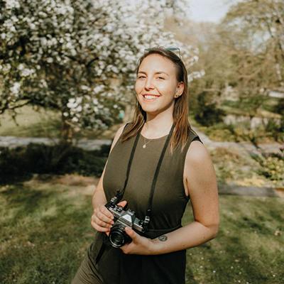 Auf dem Bild ist Frau Julia Neubauer, Fotografin abgebildet. Sie steht mit der Kamera in der Hand im Grünen und lächelt.